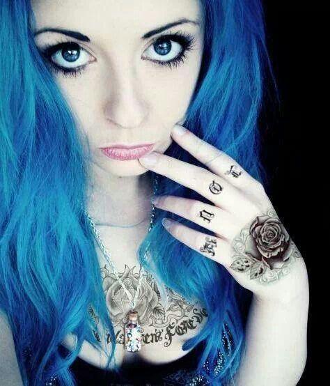 Foto de una joven de cabello azul con mirada melancólica, lleva tatuaje de rosa y letras en la amano