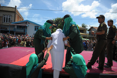 Religious officers lead a youth onstage before a public whipping in Banda Aceh, Indonesia, in August 2016