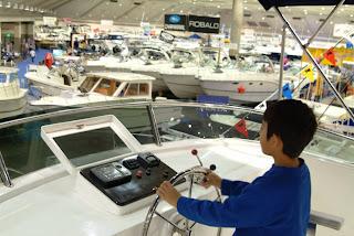 LA Boat Show child at ship steering wheel