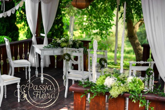 Białe, drewniane meble na ślubie plenerowym