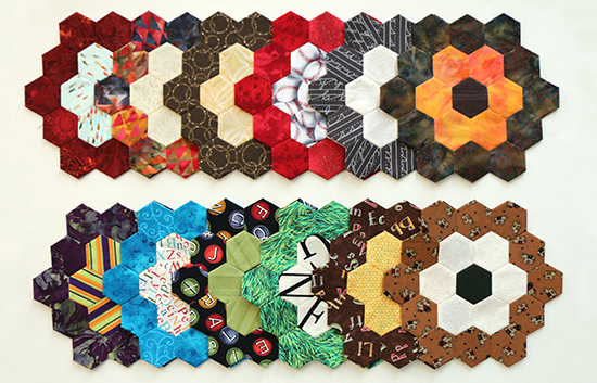 Twelve multi-colored EPP hexagon flower blocks with a light middle ring and dark outer ring arranged in two horizontal rows