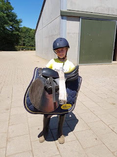 Grand daughter carrying her saddle. Courtesy of Lis Vaessen