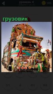 едет разноцветный грузовик обвешанный цветами