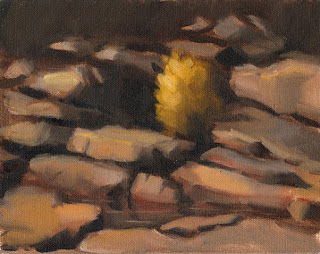 Oil painting of a small tree in amongst rocks.