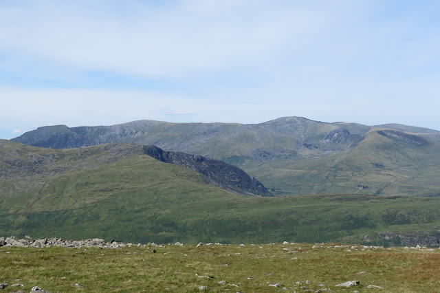 Beyond the eastern ridge of the Glyderau, the undulating top of the Carneddau mountains across the horizon.
