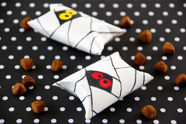 Paper tubes with mummies drawn on them and ends folded to make pillow boxes filled with dog treats