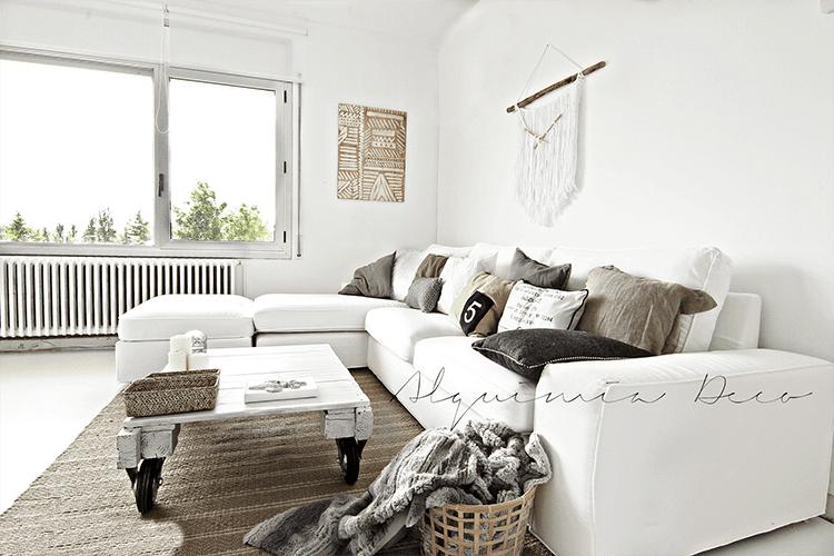 salón con sofá blanco y cojines en beige y gris