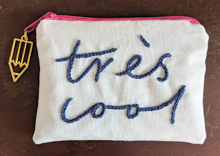 small zip purse with the words tres cool embroidered on the back and a pencil charm on the zip