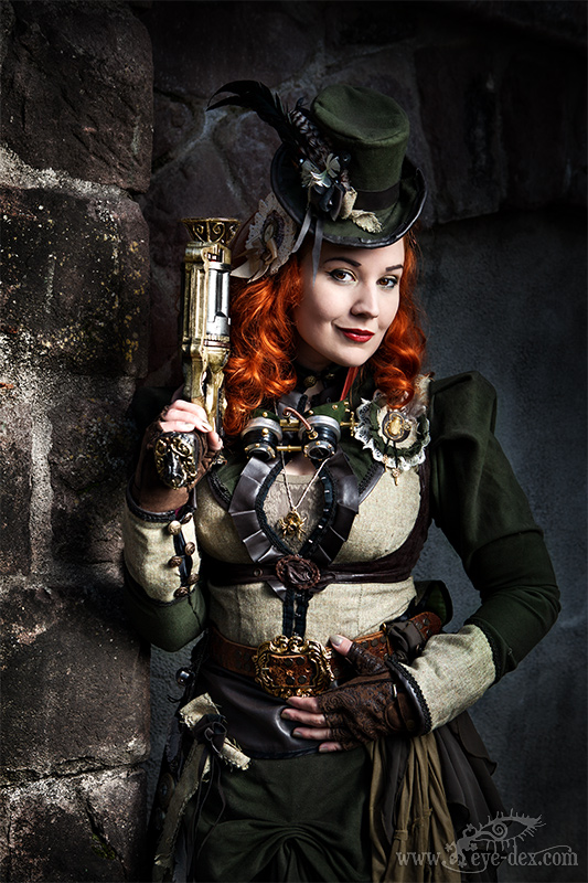 Steampunk redheaded woman wearing clothing in earth tones (colors green, gray, brown, etc.)