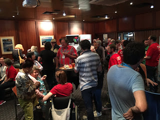 A function room full of people mingling. Many have red T-shirts. The Maker Faire volunteers wear red T-shirts.