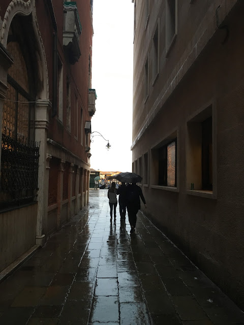 People in a Venice alley during a rain storm.