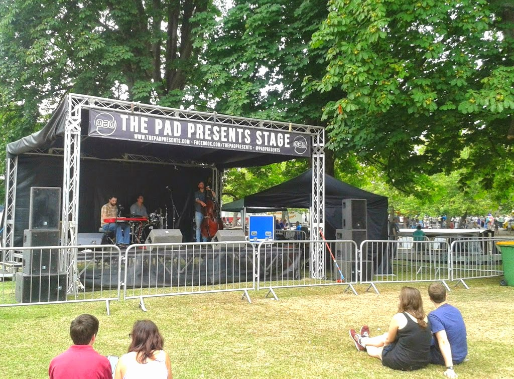 A small stage with a band performing as a market town festival