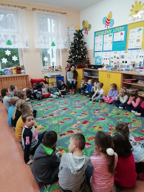 Dzieci siedząc w okręgu, słuchają bibliotekarki