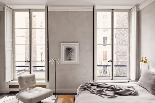 Schlafzimmer mit einem großem Bett und weißem Sessel