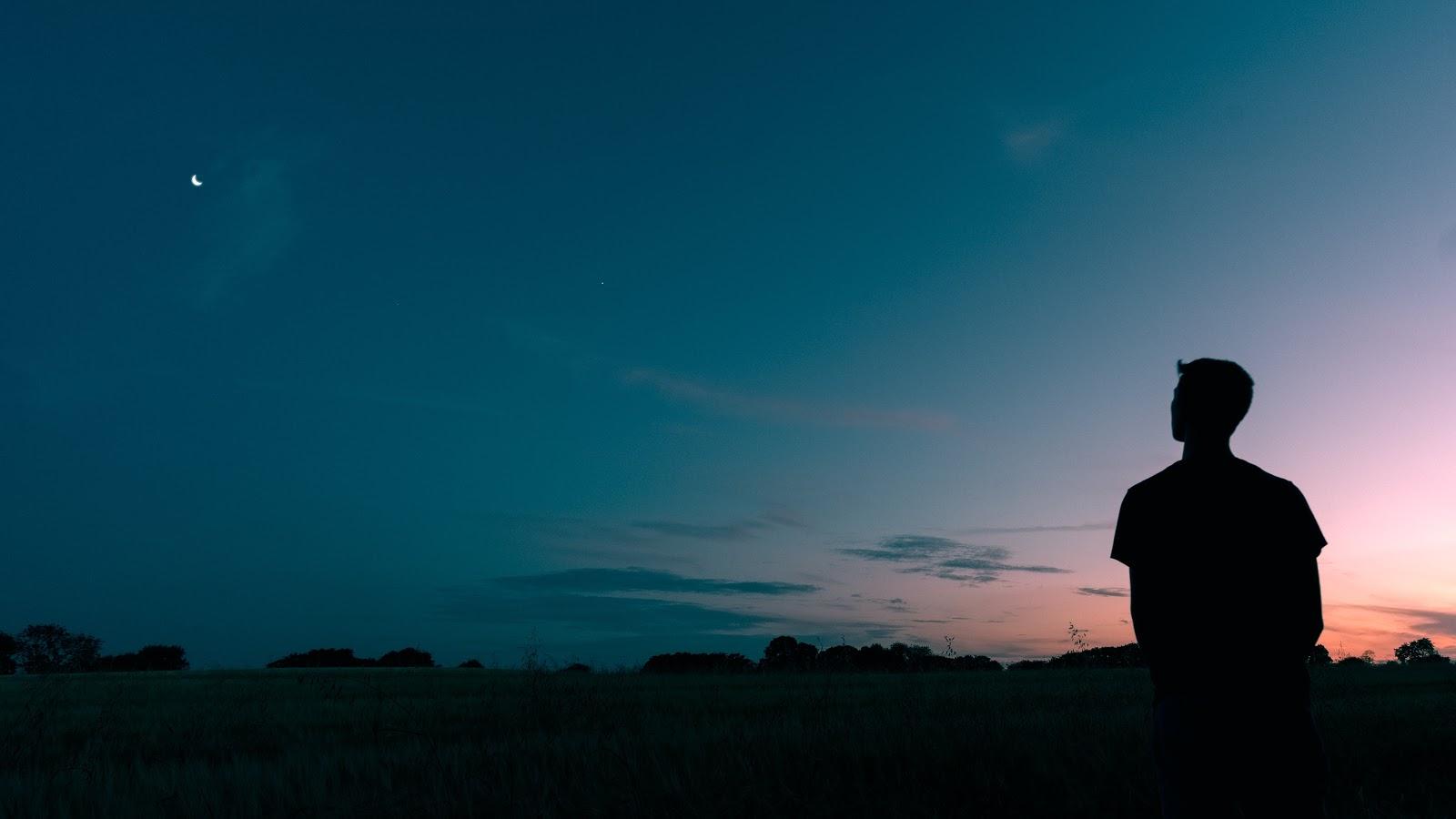 月の出た夕闇に紛れる男性の後ろ姿