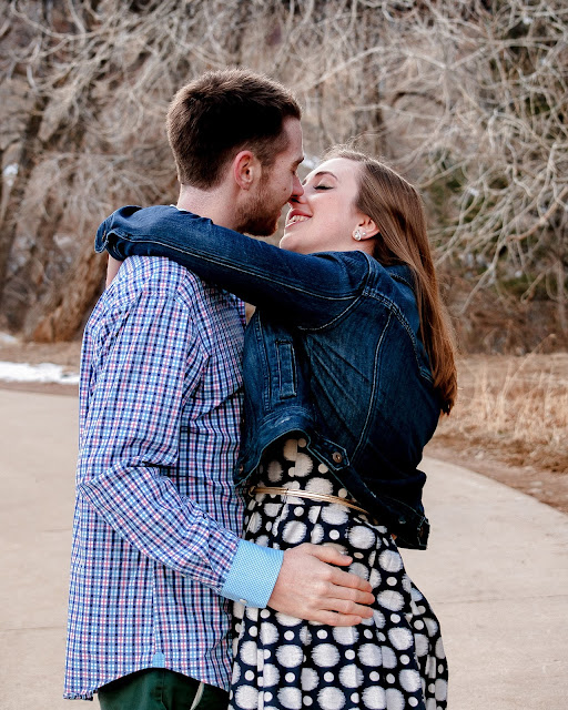 a young couples embraces for their engagement photos in Boulder Colorado