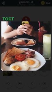 на столе лежит тост и телефон в руках парня