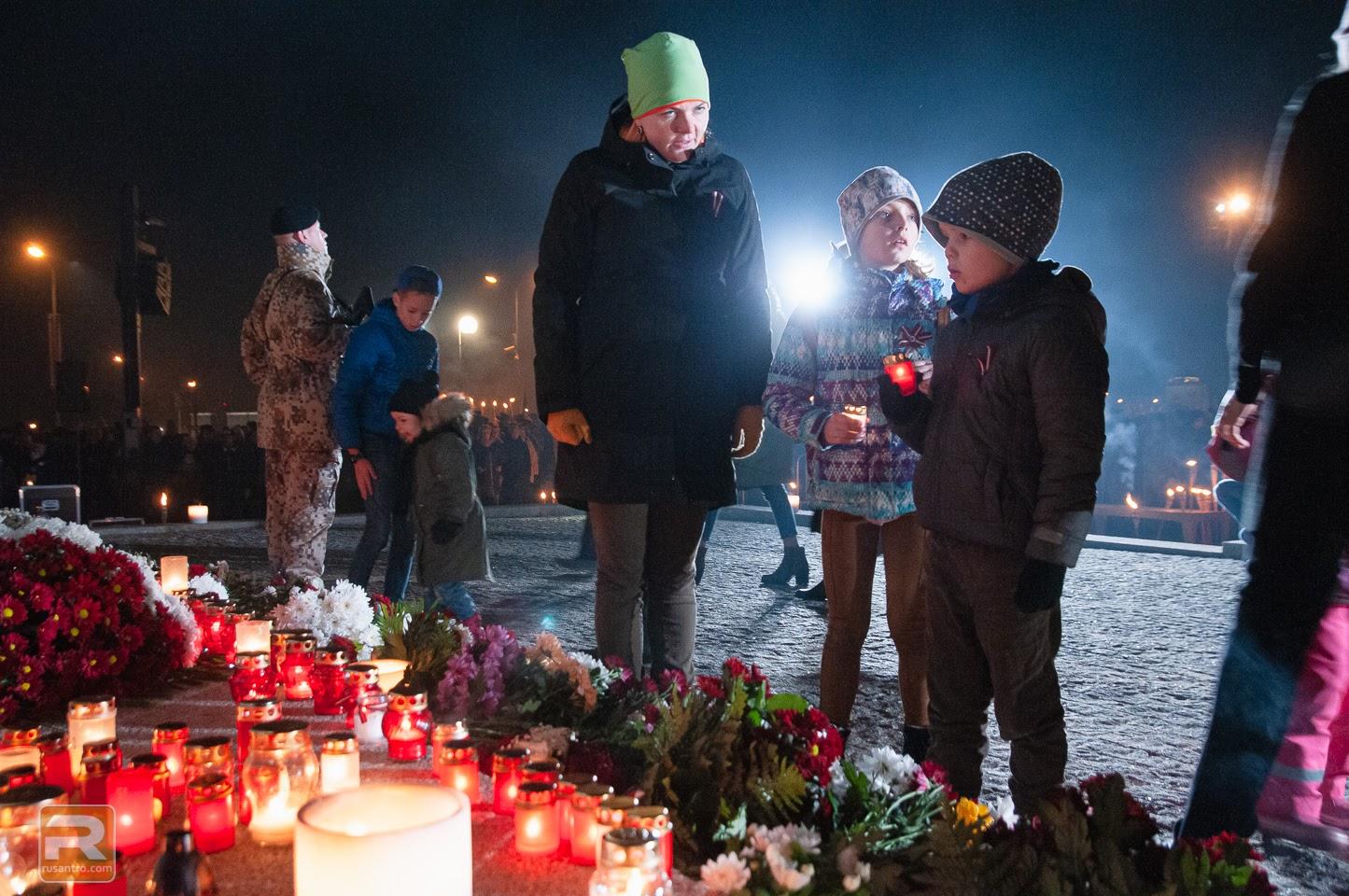 Sieviete vēro, kā viņas bērni noliek sveces pie pieminekļa