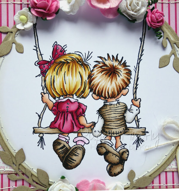 Shaped pink card with couple on swing (image from LOTV)
