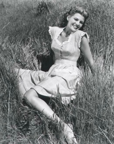 Rita Hayworth posed in summer dress lying in grass