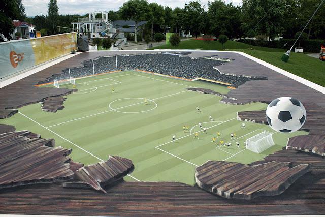 Bir stadyumun çatısından top oynanan bir futbol sahasını gösteren kaldırım sanatı resmi