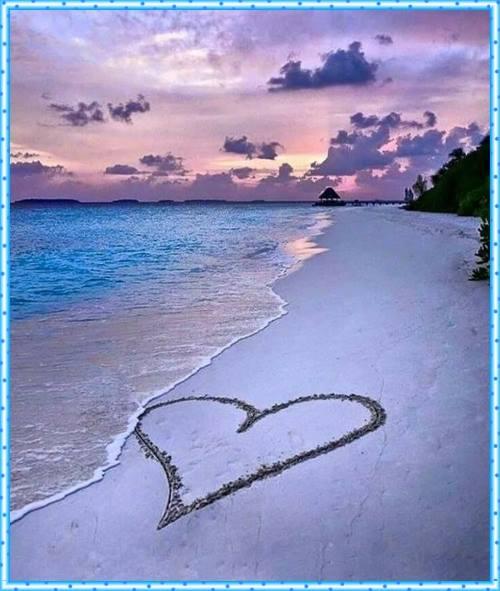 Paisagem com as ondas do mar quase alcançando um coração desenhado na areia.