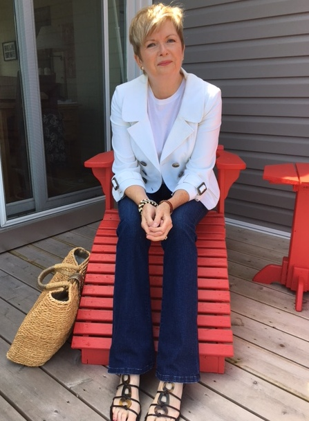 woman sitting in red Adirondack chair wearing white tee and jacket, jeans and sandals