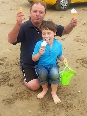 Father and son on the beach with ice creams