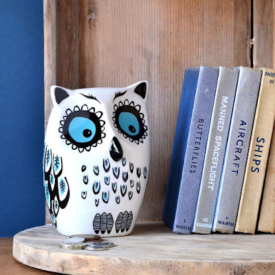 ceramic owl piggy bank, sitting on shelf next to some books