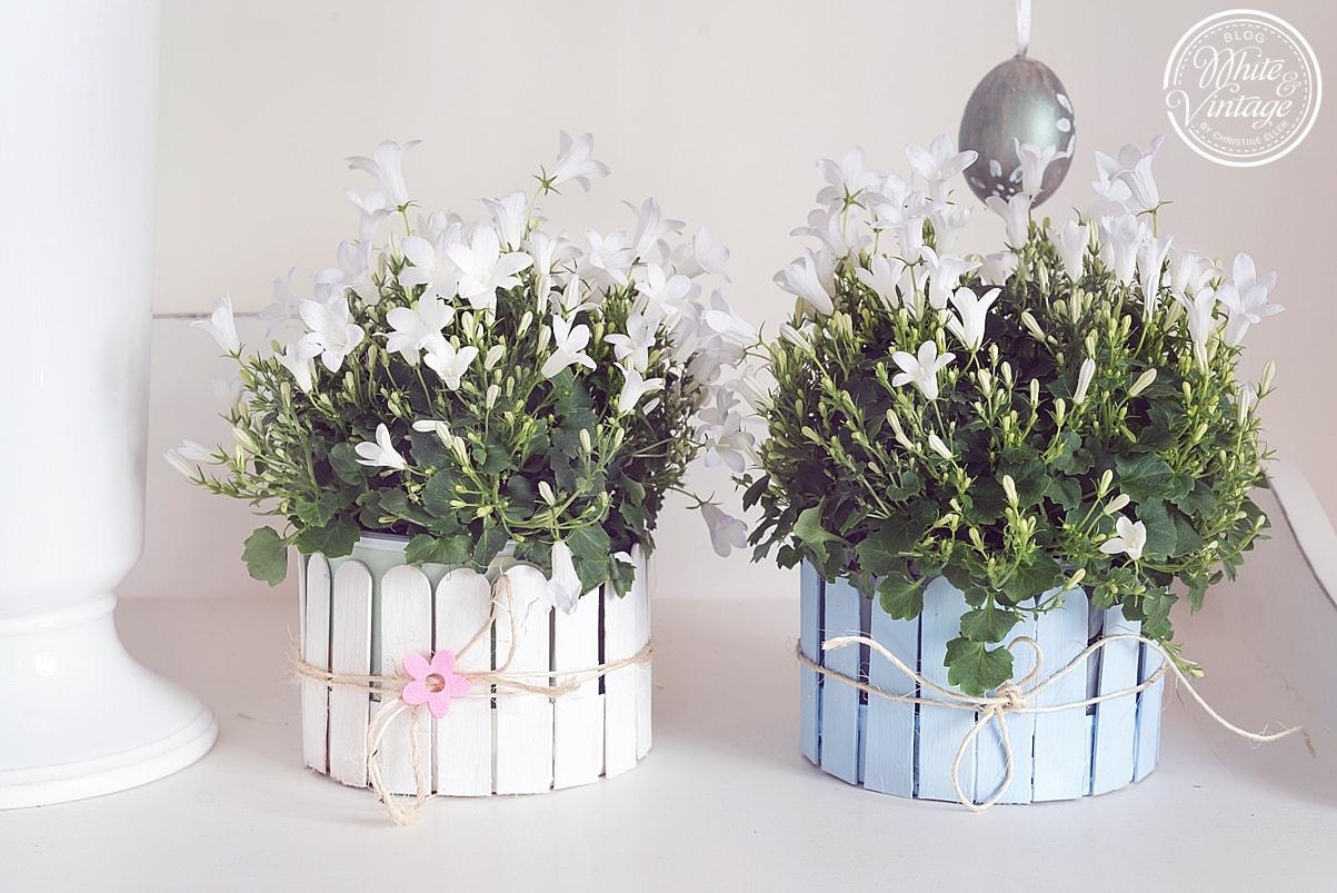 Osternest aus Eisstäbchen basteln und mit Blumen bestücken.