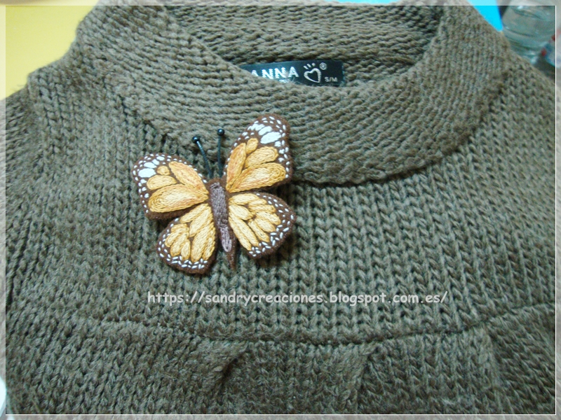 ejemplo de colocación del broche mariposa marrón en un jersey de lana