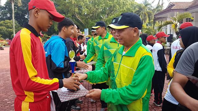 Wakil Bupati Asahan Surya menyerahkan penali kasih kepada atlet berprestasi.