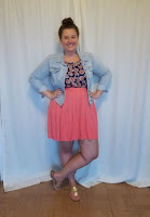 an outfit with a blue floral top, denim jacket, pink skirt, and gold sandals