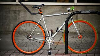 silver and orange bicycle locked to bike rack
