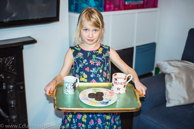 A young girl holding a tray with 2 mugs on and a plate with 3 oreo cookies
