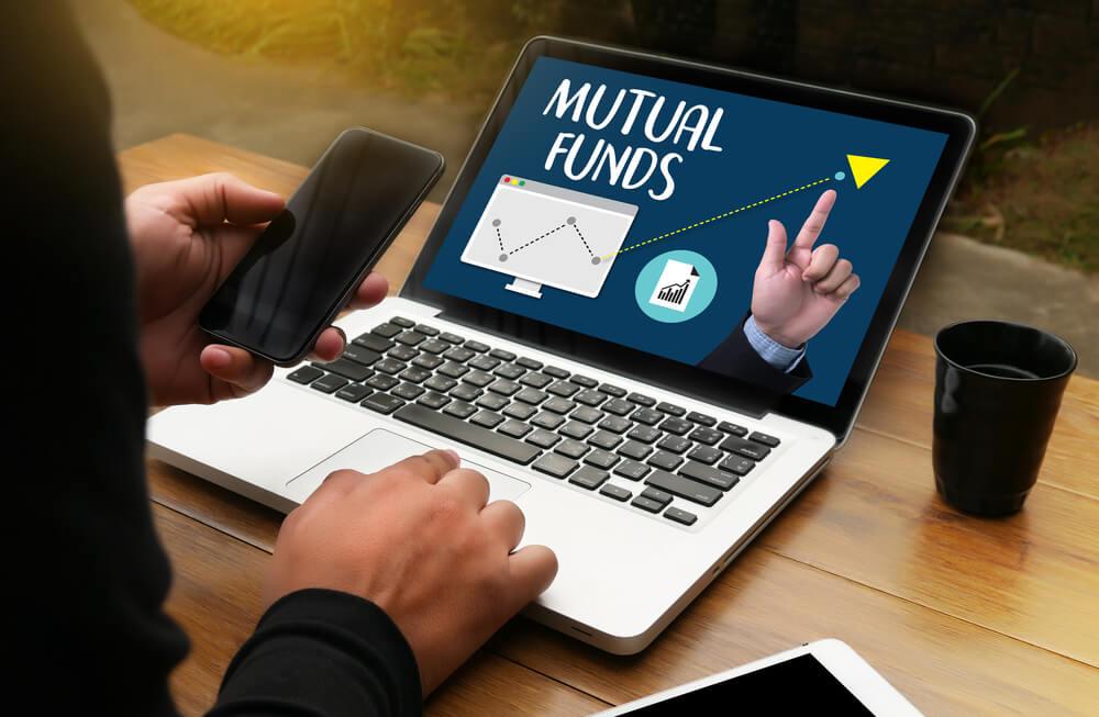 mutual funds written on a man's laptop