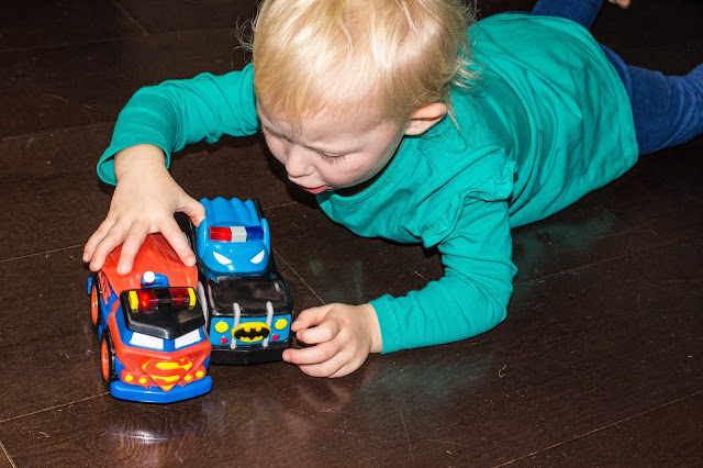 A preschooler on the floor playing with a superman and a batman Herodrives mash machine cars
