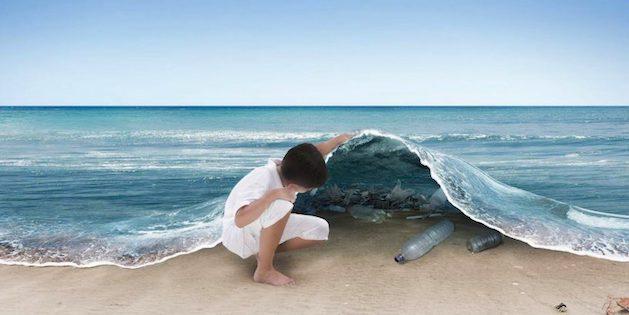 niño observa basura plástica en el mar
