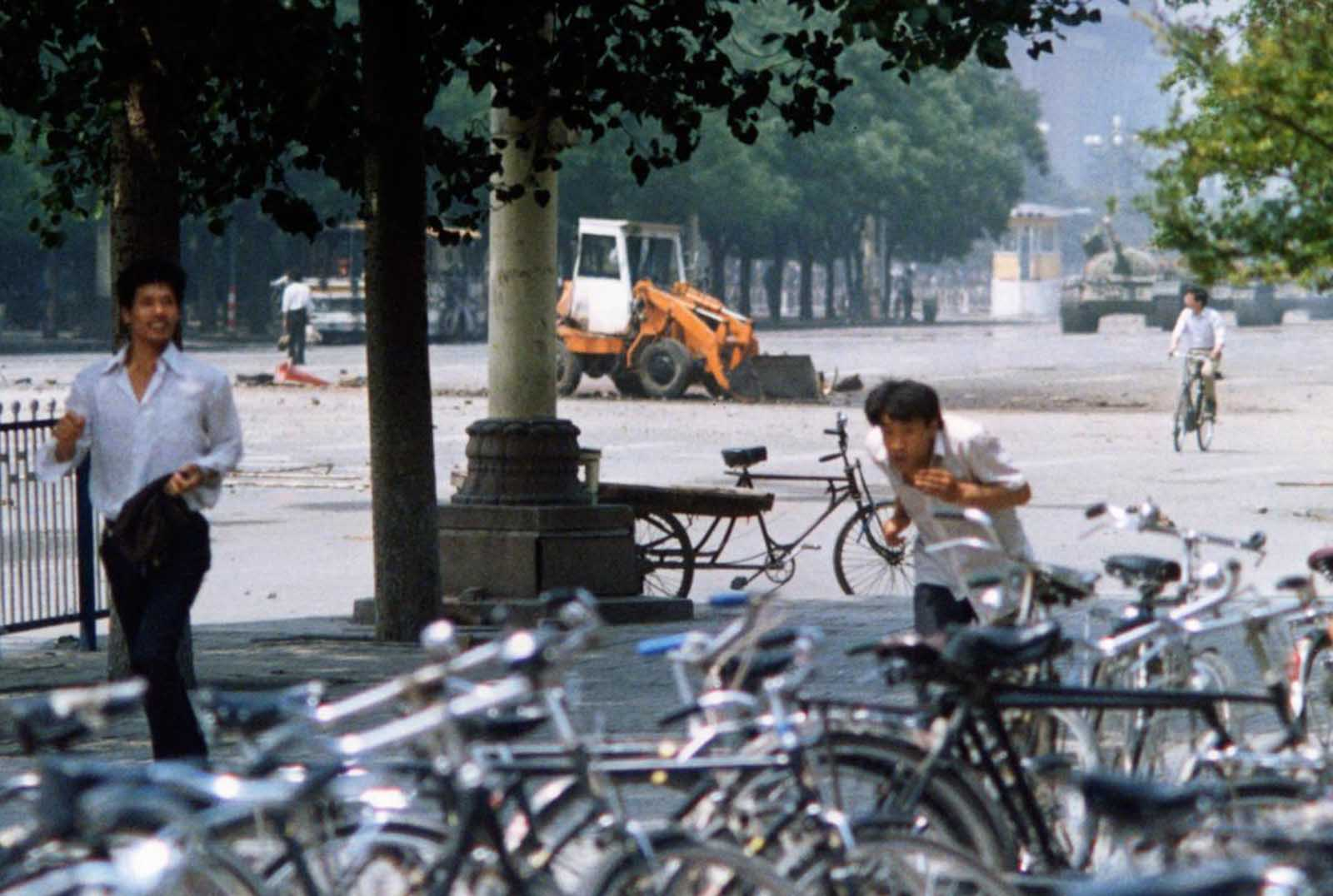 1 of 2) Three unidentified men flee as a Chinese man, background left, stands alone to block a line of approaching tanks, in Beijing's Tiananmen Square, on June 5, 1989. The man in the background stood his ground and blocked the column of tanks when they came closer, an image captured on film by numerous other photographers and one that ultimately became a widely reproduced symbol of events there.
