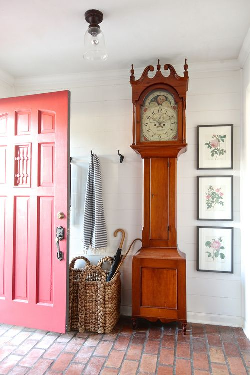 Cozy entry with brick floor and antique grandfather clock. And that red door is gorgeous!
