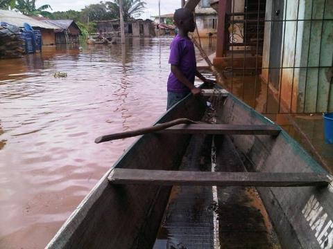 Child with boat in an Anam village during flood 2012