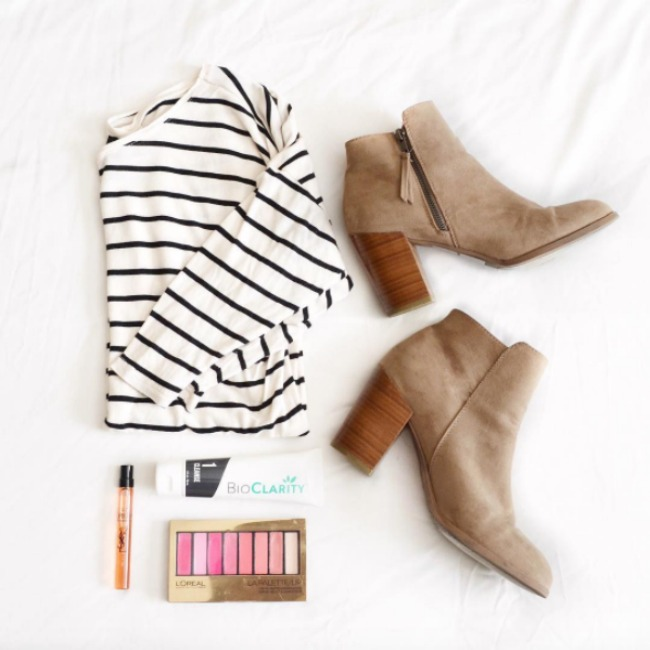 A fashion flat lay featuring a black and white striped tshirt, faux suede booties, bioclarity, ysl black opium perfume, and the l'oreal pink lip palette