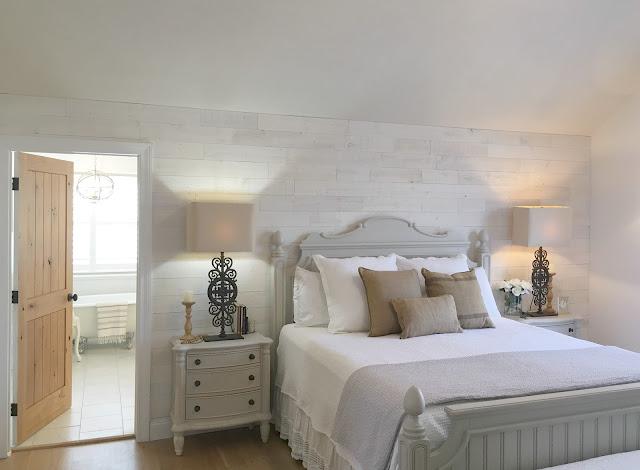 Knotty alder door in master bedroom open to white modern farmhouse style bathroom renovation by Hello Lovely Studio