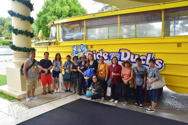 group of adults taking photo in front of a large yellow vehicle