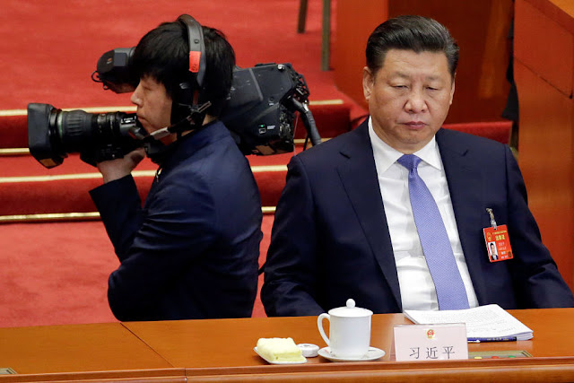 Image Attribute: A cameraman stands next to China's President Xi Jinping during the opening session of the National People's Congress (NPC) at the Great Hall of the People in Beijing, China, March 5, 2017. REUTERS/Jason Lee