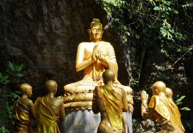 a statue of Buddha teaching his disciples