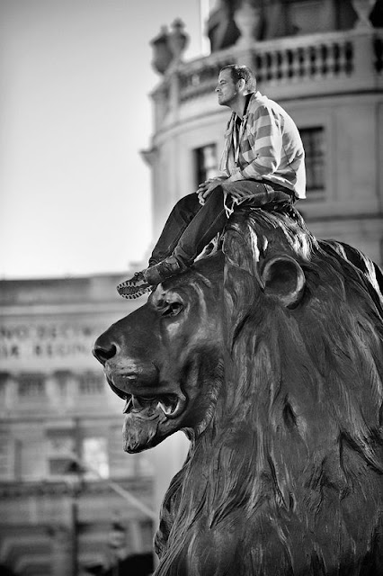 Man sat on metal lion statue's head