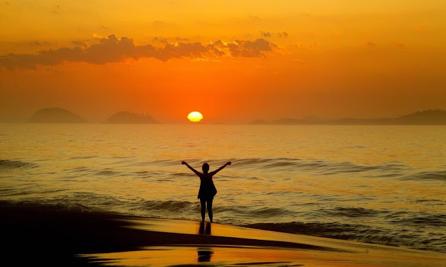 amanhecer na praia com mulher nas ondas doa praia