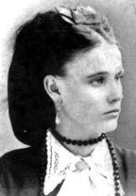 A Victorian-era portrait of a beautiful, elagant-looking young white woman with dark hair, pearl drop earrings, and a lace collar
