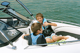 Two twin boys sitting at the bow of the speedboat at Castaic Lake